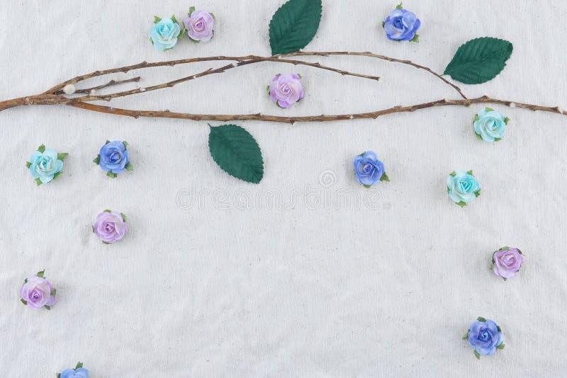 Il ramo di Brown decora con i fiori di carta e le foglie verdi della rosa blu del tono fotografie stock libere da diritti