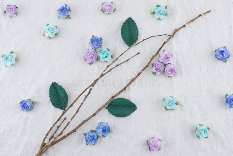Il ramo di Brown decora con i fiori di carta e le foglie verdi della rosa blu del tono immagini stock libere da diritti