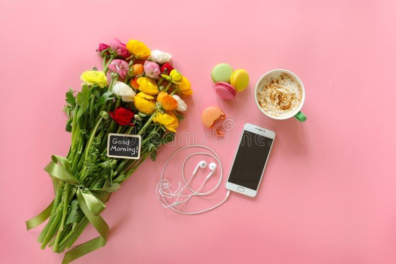 Il ranuncolo festivo di concetto di mattina fiorisce con il buongiorno della nota, la tazza di cappuccino, il makaron del dolce e fotografia stock