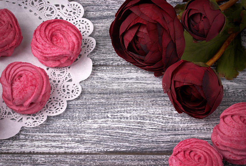 Il ranuncolo rosso fiorisce il tovagliolo di carta di pizzo dello zefiro delle caramelle gommosa e molle bianche e rosa del ranun immagini stock