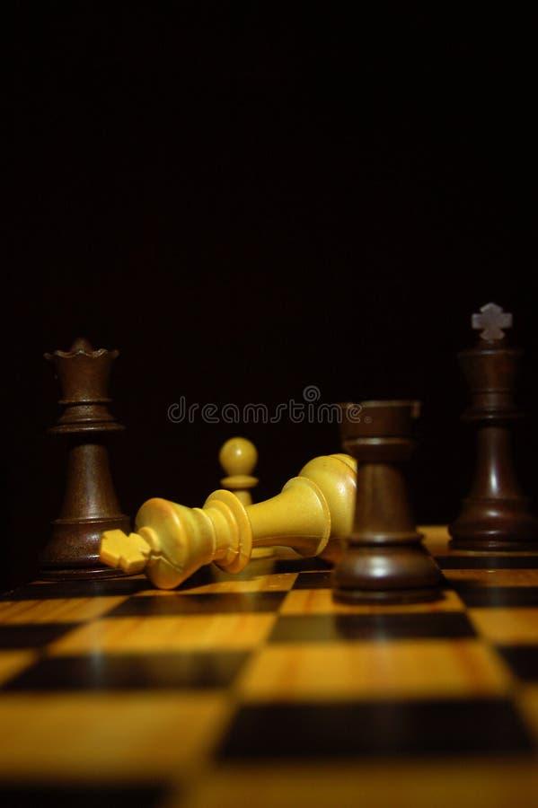 Il re bianco perde ad un compagno del controllo in un gioco di scacchi su un bordo di legno fotografia stock libera da diritti