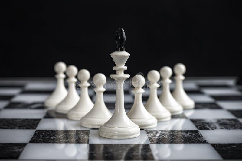 Il re ed i pegni su una scacchiera su un fondo scuro fotografie stock libere da diritti