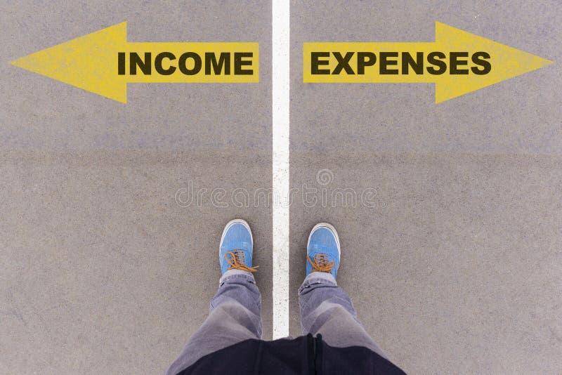 Il reddito contro le spese manda un sms alle frecce sulla terra, sui piedi e sulle scarpe dell'asfalto fotografia stock
