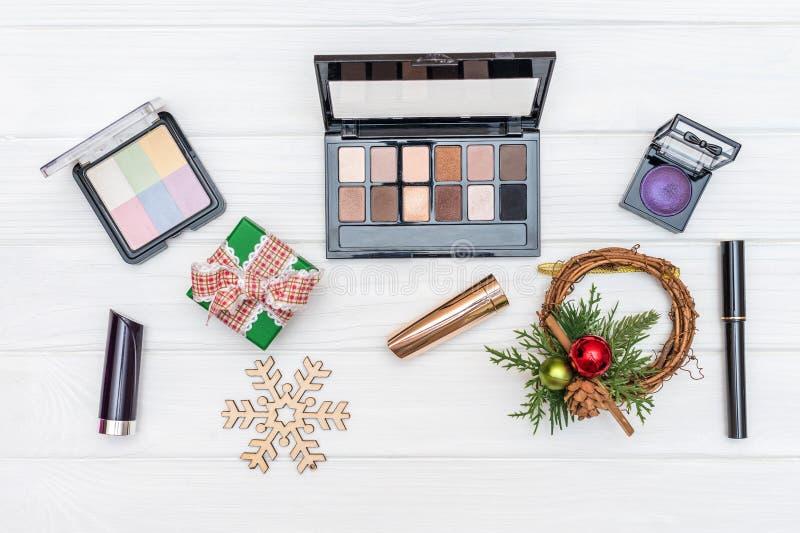 Il regalo compone, cosmetici ed ornamenti e giocattoli del nuovo anno su fondo di legno bianco immagini stock
