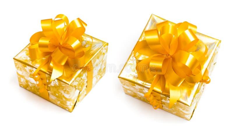 Il regalo ha imballato in documento dorato con l'arco giallo immagine stock libera da diritti