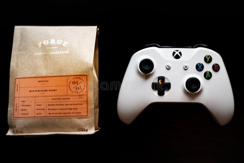 Il regolatore dei giochi dello Xbox One si è seduto accanto ad una borsa di caffè macinato contro un fondo nero scuro immagini stock libere da diritti
