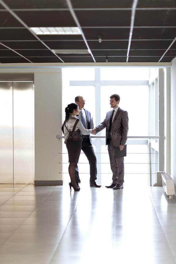 Il responsabile accoglie favorevolmente il cliente nell'ufficio dell'ingresso fotografia stock