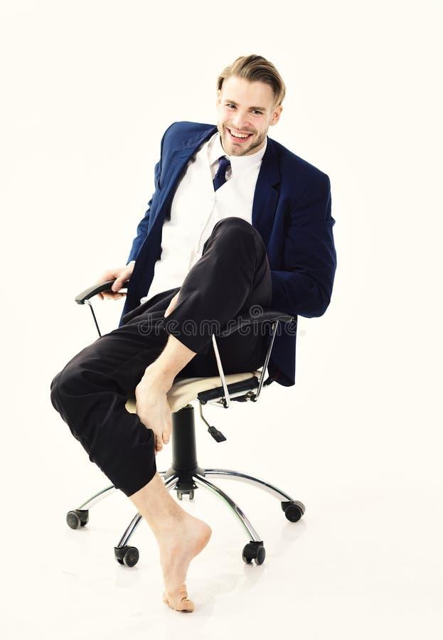Il responsabile con la barba ed il fronte sicuro si siede in sedia Uomo nei sorrisi convenzionali dell'attrezzatura isolato su fo immagini stock