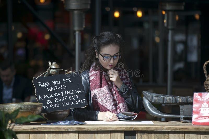 Il responsabile del ristorante legge il menu in attesa degli ospiti Il piatto dice: immagine stock libera da diritti