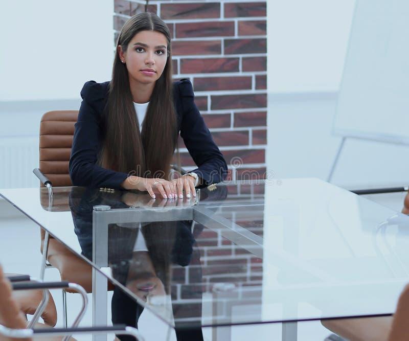 Il responsabile della donna sta sedendosi alla tavola immagine stock libera da diritti