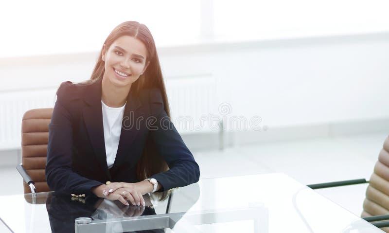 Il responsabile della donna sta sedendosi alla tavola fotografie stock