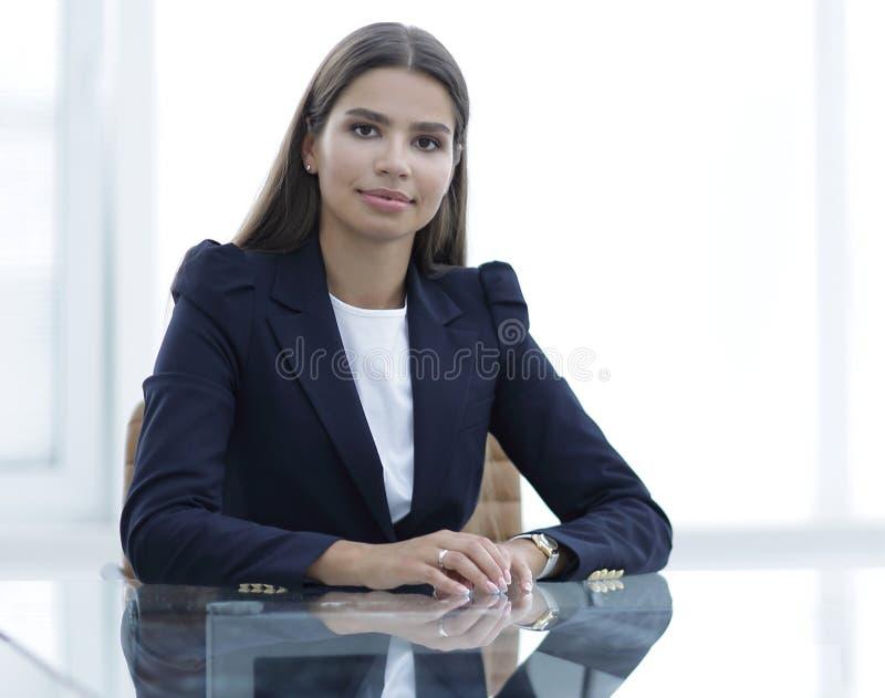 Il responsabile della donna sta sedendosi alla tavola fotografia stock