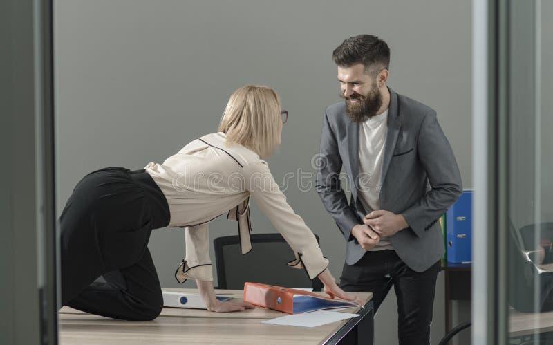Il responsabile di ufficio seduce il capo sul desktop Concetto romanzesco e sessuale dell'ufficio del flirt fotografia stock