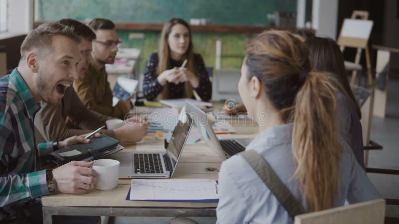 Il responsabile femminile viene a team, si siede alla tavola e stringe la mano al collega maschio Gruppo creativo di affari all'u fotografia stock