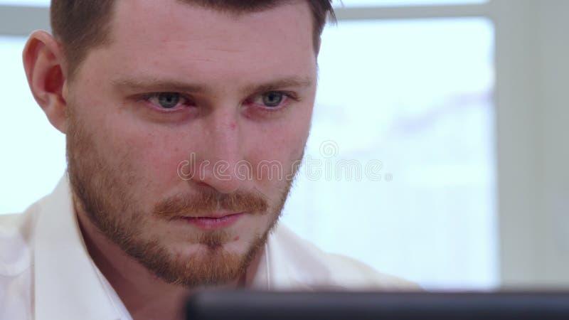 Il responsabile maschio esamina lo schermo del computer portatile fotografia stock