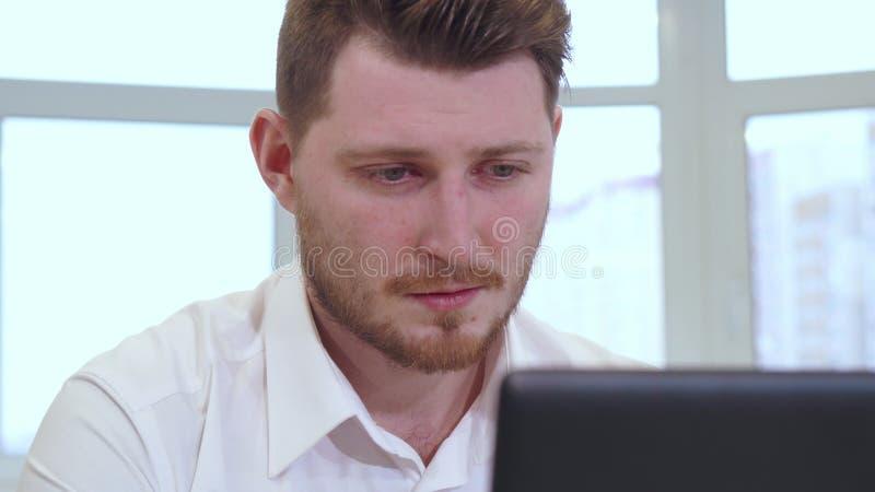 Il responsabile maschio utilizza il computer portatile all'ufficio immagine stock libera da diritti