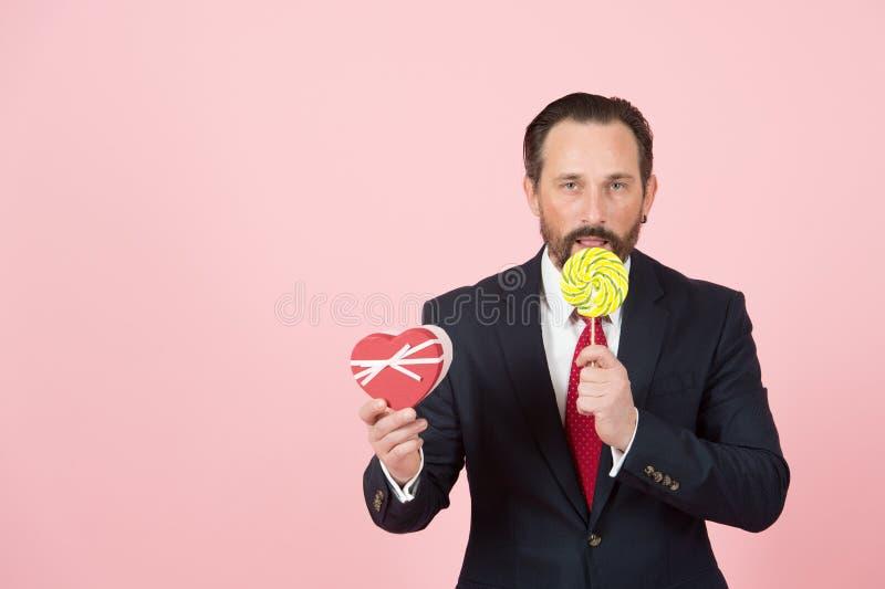 Il responsabile professionista prova la lecca-lecca arancio Equipaggi la caramella di amori e fa il presente con cuore inscatolar immagini stock