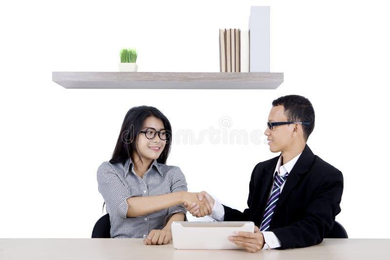 Il responsabile stringe le mani con il suo impiegato immagine stock