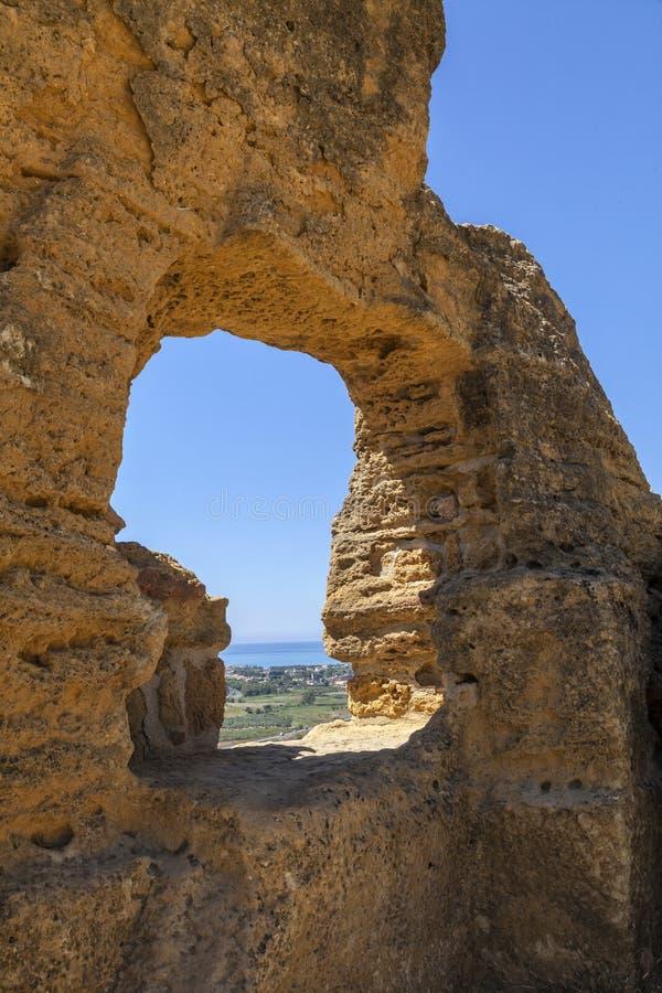 Il resti dei mura di cinta del greco antico Akragas come finestra sul panorama Il mare come fondo Agrigento, Sicilia, fotografia stock libera da diritti