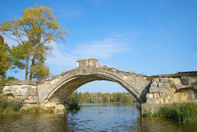 Il resti di vecchio ponte a dorso d'asino sul lago bianco Parco di Gatcina, Russia immagini stock libere da diritti