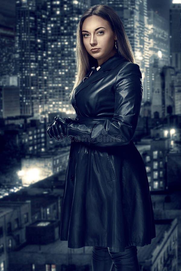 Il retro ritratto di bella donna inaccessibile in mantello nero sta contro lo sfondo della città di notte Film noir fotografia stock