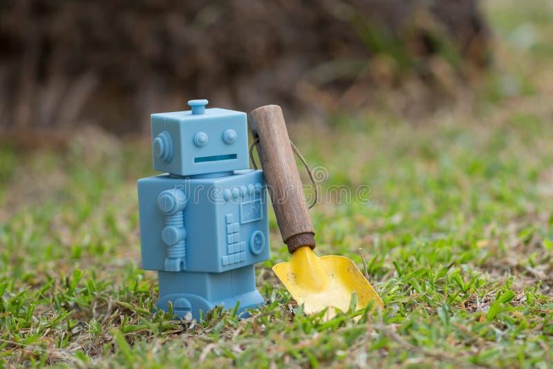 Il retro robot blu gioca con gli strumenti di giardino in foglie verdi naturali fotografie stock libere da diritti