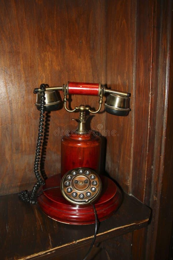 Il retro vecchio telefono rotatorio rosso sulla parte anteriore della tavola ha strutturato la parete di legno immagini stock libere da diritti