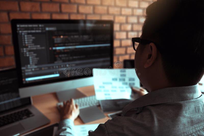 Il retrovisore degli sviluppatori di software sta lavorando ad una tastiera di computer e sta analizzando il codice scritto nel p fotografia stock