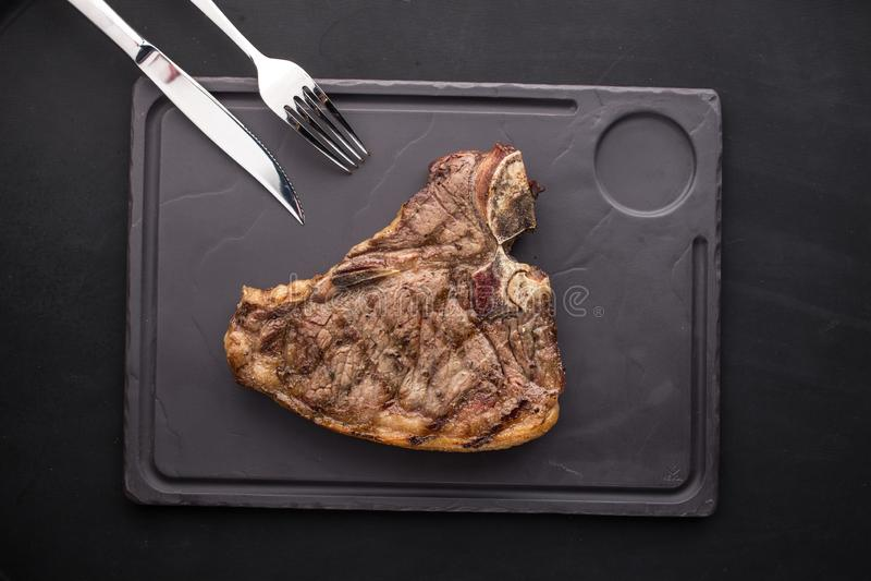 Il ribeye grigliato rinforza la bistecca con la forcella ed il coltello sul piatto di pietra su fondo nero immagine stock