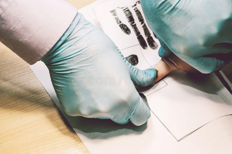 Il ricercatore prende le impronte digitali dal sospetto nel crimine La ricerca è un crimine crimine fotografia stock libera da diritti