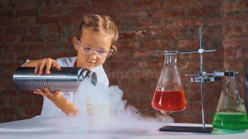 Il ricercatore sveglio del bambino sta eseguendo un esperimento con azoto liquido fotografia stock