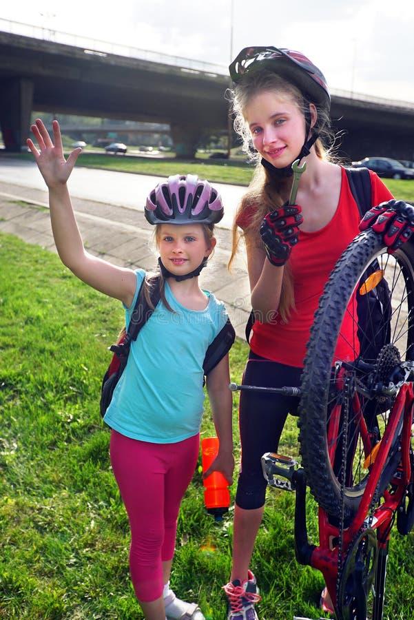 Il riciclaggio dei bambini delle ragazze pompa sulla gomma della bicicletta immagine stock libera da diritti