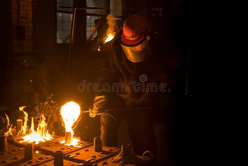 Il riempitore del metallo nel casco cola la lega liquida dalla siviera nello stampo immagini stock libere da diritti