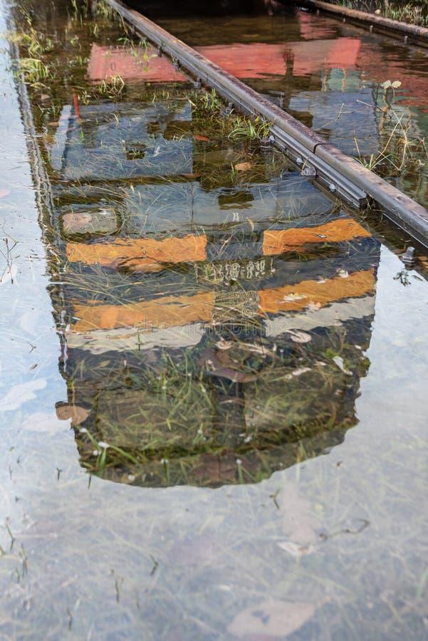 Il riflesso di una locomotiva blu sulle rotaie in acqua fotografia stock libera da diritti