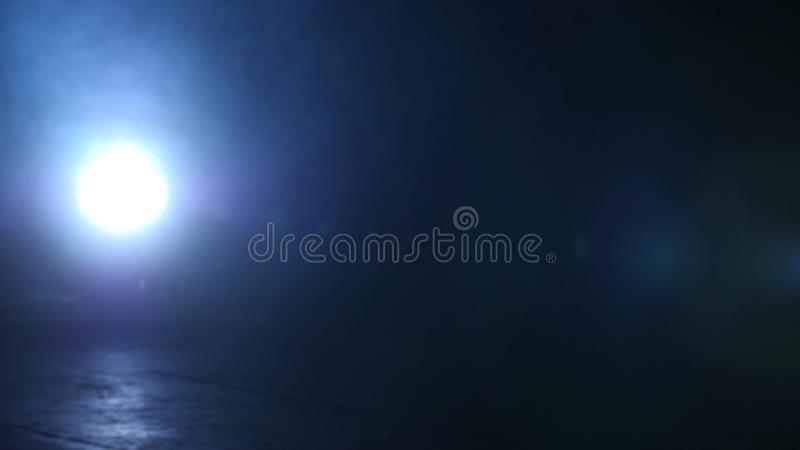Il riflettore luminoso splende nello scuro Movimenti della macchina fotografica da destra a sinistra che catturano destra brillan immagine stock