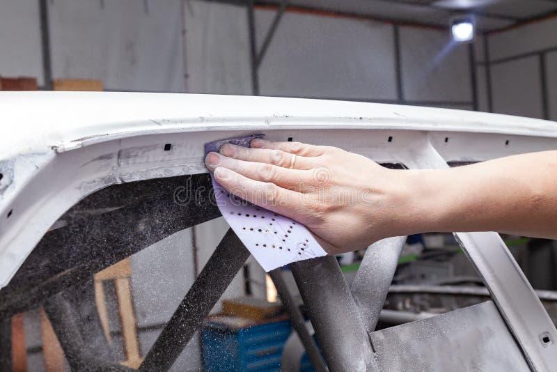 Il riparatore del corpo frantuma la struttura dell'automobile bianca con la carta di smeriglio porpora in preparazione di pittura immagine stock