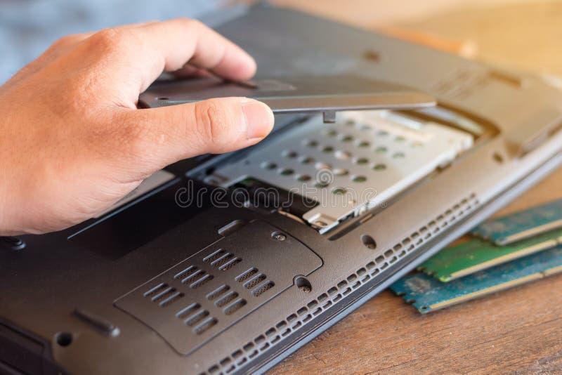 Il riparatore ristabilisce il computer portatile, installante l'hardware del disco rigido fotografie stock
