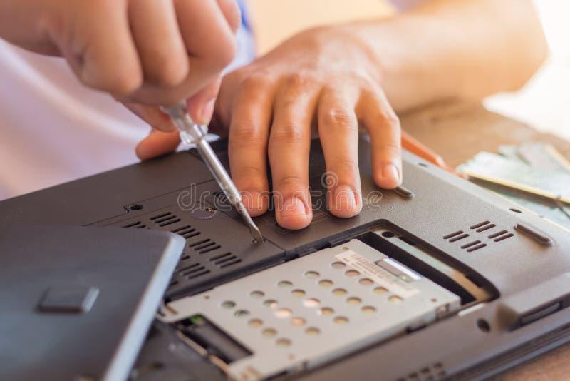 Il riparatore ristabilisce il computer portatile, installante l'hardware del disco rigido fotografia stock