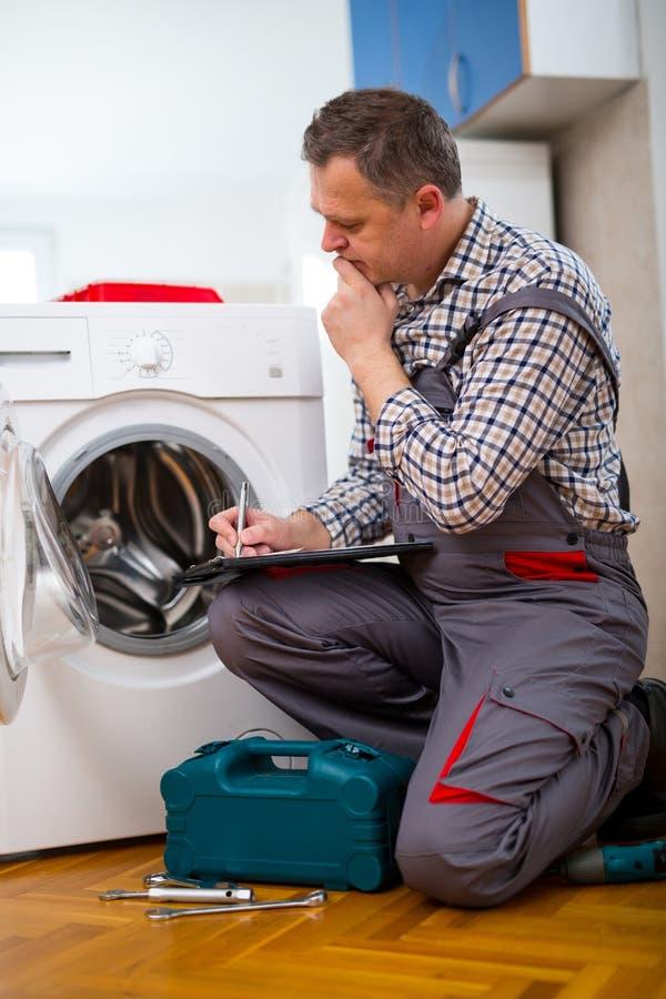 Il riparatore sta riparando una lavatrice sui precedenti bianchi fotografia stock
