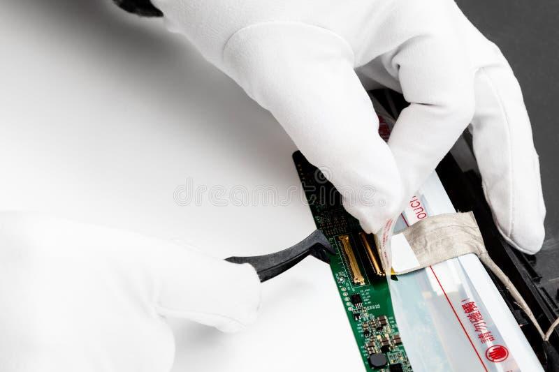 Il riparatore stacca i contatti dello schermo del computer portatile fotografia stock