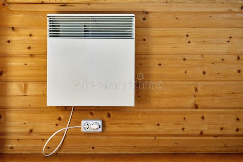 Il riscaldatore a aria elettrico su una parete di legno si è collegato alle condutture all'interno fotografie stock