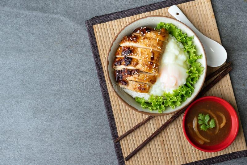 Il riso del pollo o il pollo e l'uovo di Teriyaki onsen in ciotola grigia con la salsa dell'ostrica sulla tavola fotografia stock