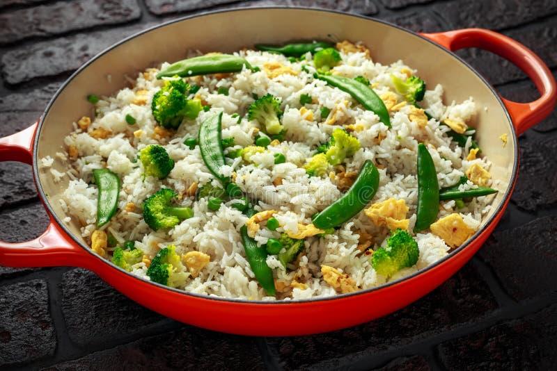 Il riso fritto con le verdure, i broccoli, i piselli e le uova è servito in una pentola Alimento sano immagine stock