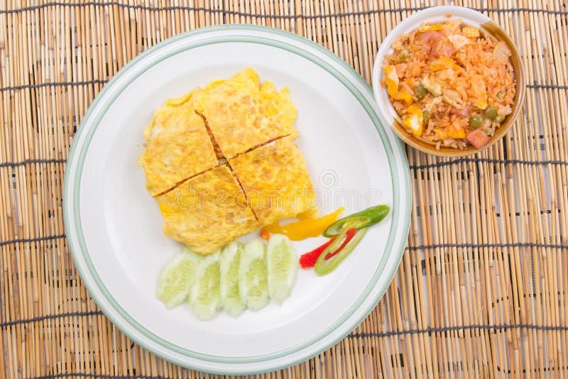 Il riso infornato con l'involucro del bacon eggs sul piatto bianco immagini stock libere da diritti