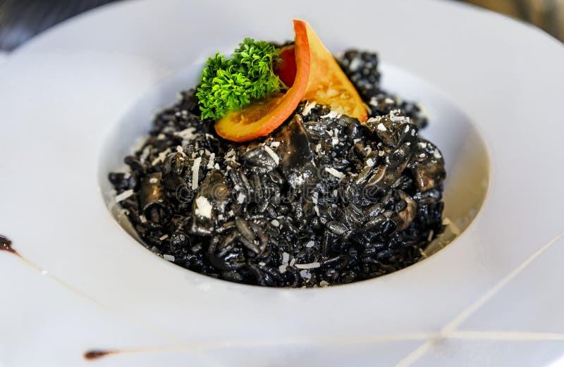 Il risotto dell'inchiostro del calamaro con gli anelli del calamaro, è servito con una fetta e un prezzemolo arancio ad un ristor fotografia stock libera da diritti