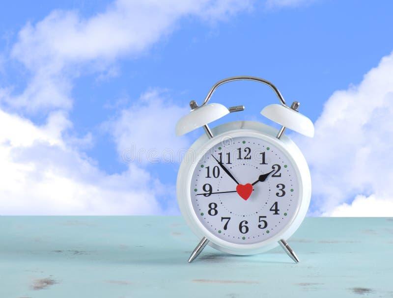 Il risparmio di luce del giorno cronometra l'orologio bianco con il fondo del cielo fotografie stock libere da diritti