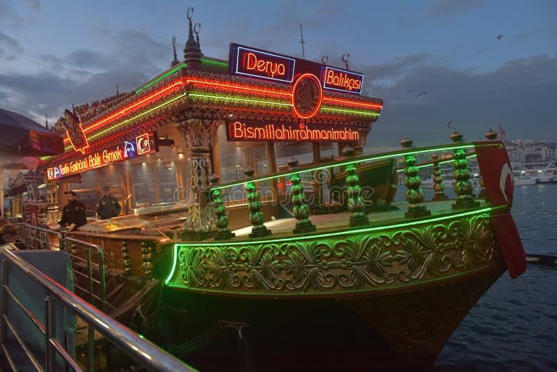 Il ristorante di galleggiamento del pesce, attraccato al pilastro di Eminonu, alle luci uguaglianti variopinte immagini stock