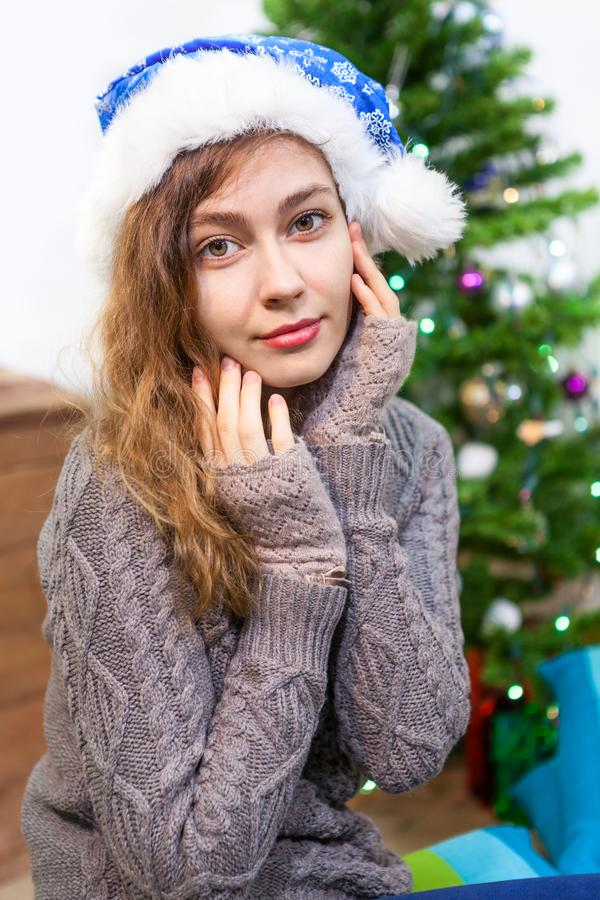 Il ritratto abbastanza caucasico della giovane donna con le mani si avvicina al fronte, Natale fotografia stock libera da diritti
