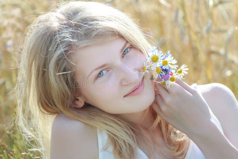 Il ritratto all'aperto dell'estate di gran lunga della ragazza bionda alle orecchie del cereale sistema il fondo fotografie stock