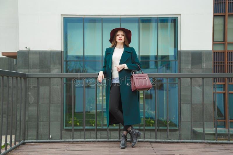 Il ritratto alla moda della giovane donna in vestito verde smeraldo, bianco ha tricottato il maglione ed il cappello di Marsal fotografia stock